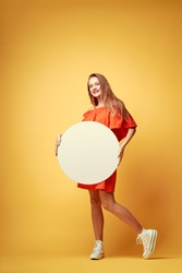 Your text here. Colorful studio portrait of pretty young woman showing round empty blank board with copy space against yellow background.