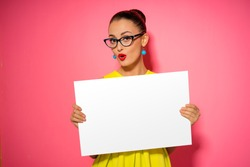 Your text here. Pretty young excited woman holding empty blank board. Colorful studio portrait with pink background.