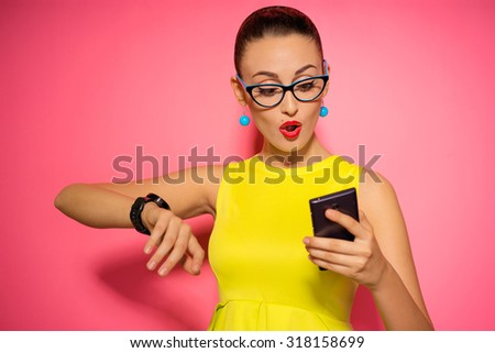 Youth and technology. Amazed young woman with smartwatch using mobile phone. Colorful studio portrait. Pink background.