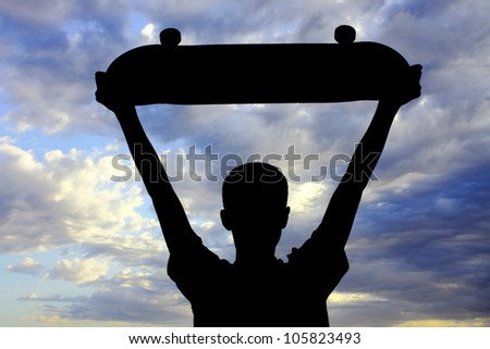 Youth boy expressing himself with raised skateboard gesture while looking at a very vivid sky with striking cloud formation (silhouette).