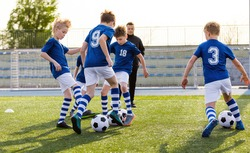 Youth Football Club Training Unit. Kids Practicing Football With Young Coach. Group of Kids Playing Training Drill. Hapy Sporty Boys in Blue Soccer Jersey Shirts