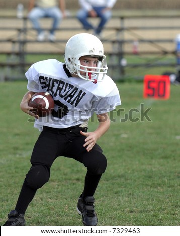 Youth football player crossing the 50 yard line on a running play.