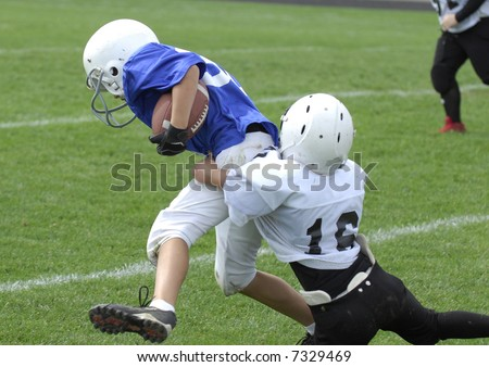Youth football player tackles another. - stock photo