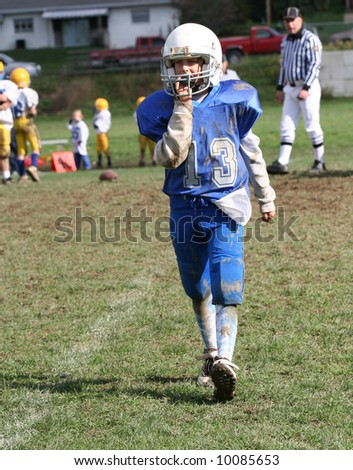 Youth Football Player Walking Off Field During Game.