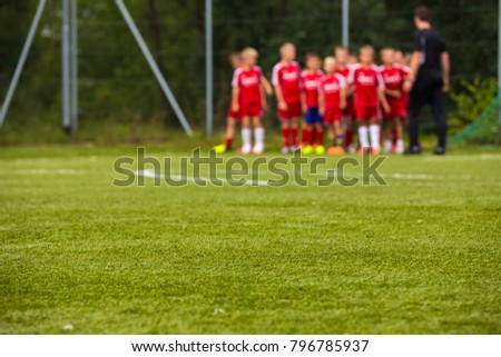 Youth Football Team with Coach on Pitch; Blurred Soccer Background. Soccer Training Session for Kids; Young Football Players Listening Coach Before the Training Match.  #796785937