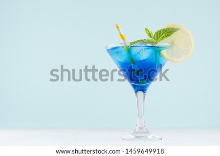 Youth fresh alcohol blue Hawaii cocktail with licor curacao, ice cube, lemon slice, yellow straw in wine glass on mint background, white wood board. Foto stock ©