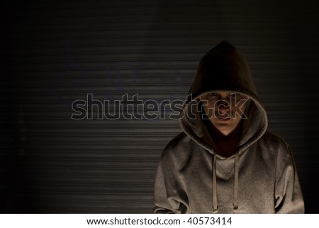 Youth in hooded top in front of garage door with graffiti.