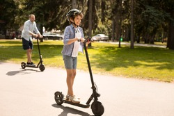 Youth Leisure Concept. Full length portrait of excited boy riding black e-scooter with his dad in background, free space