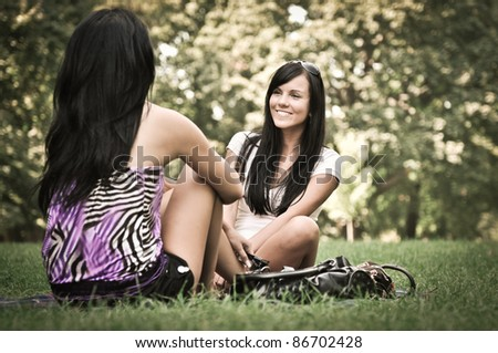 Youth lifestyle park scene - two young friends (girls) talking outdoors. Siting on rug laid in grass. - stock photo