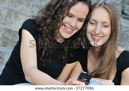 Youth lifestyle - two smiling friends (girls) outdoors with mobile phone