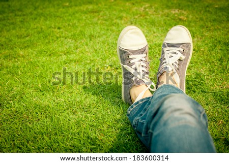 youth sneakers on girl legs on grass during sunny serene summer day. #183600314