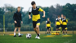 Youth Sports Player Running on Training Field. Junior Football Club Practice Session. Teenagers in Soccer Training Sportswear with Young Coach. Sports Educational Equipment