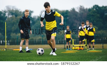 Youth Sports Player Running on Training Field. Junior Football Club Practice Session. Teenagers in Soccer Training Sportswear with Young Coach. Sports Educational Equipment Stock photo ©
