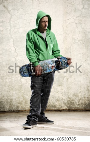 Youth stands with skateboard and green hoodie