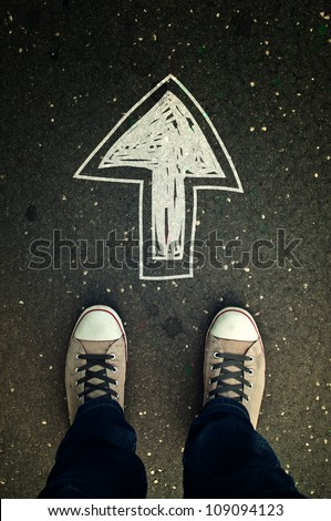 Youth street lifestyle. Male sneakers on asphalt road with drawn direction arrow as millennial education guidance, student guide, consultation and advisory, top view.