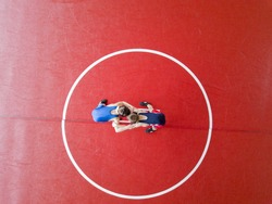 Youth wrestlers hand fighting on the mat. View from above.