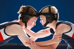 Youth wrestlers hand fighting on their feet