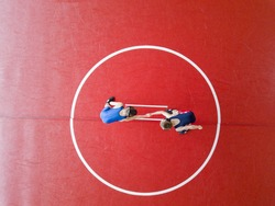 Youth wrestlers shaking hands on the mat. View from above.