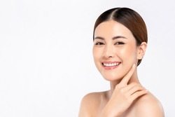 Youthful bright skin smiling pretty Asian woman with hand touching face on white background for beauty concepts