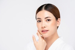 Youthful radiant pretty Asian woman with hand touching face on white background for beauty and skin care concepts