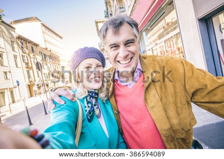 Youthful senior couple taking selfie outdoors - Happy mature pair having fun while walking on the streets outdoors