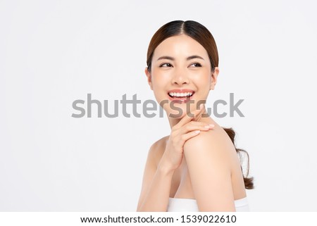 Youthful smiling Asian woman with hand touching face isolated on white background for beauty and skin care concepts