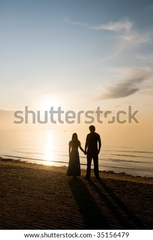 Youths  man and woman stand ashore sea and look at sunset.