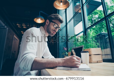 Photo of Yow angle view of a young stylish well dressed author writer is working in a modern coworking, writing the novel, in glasses, so serious and focused
