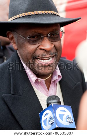 YPSILANTI, MI - NOVEMBER 10: Republican Presidential candidate Herman Cain speaks to a reporter on November 10, 2011 in Ypsilanti, MI