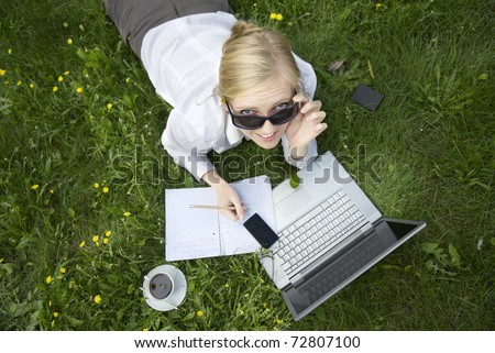 ypung woman working outside on computer