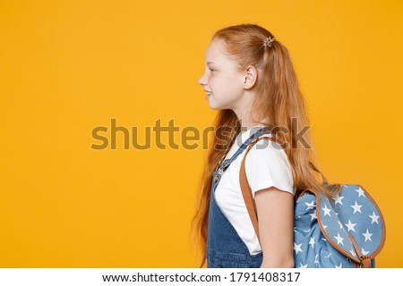 YSide profile view young redhead school teen girl 12-13 years old pony tails in white t-shirt blue denim uniform backpack isolated on yellow background children studio portrait Kids education concept. Stock photo ©