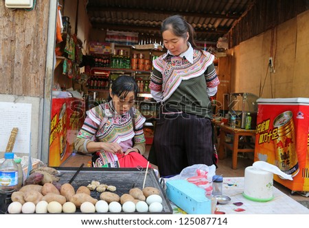 YUANYANG - DECEMBER 16: Food stall vendors dressed in traditional costumes from the Yii ethnic minority wait for customers at their shop on Dec 16, 2012 in Yuan Yang County, China. - stock photo