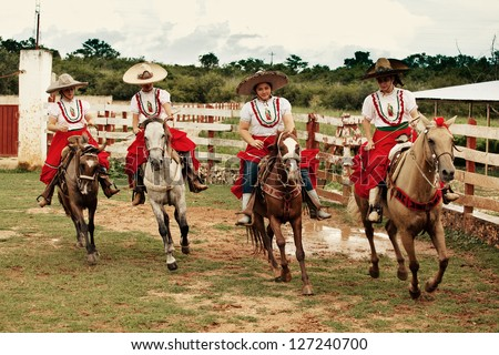 YUCATAN, MEXICO - AUGUST 15: Young unidentified Girls in a Escaramuza Charra, a famous type of traditional Rodeo in Mexico on August 15, 2012 in Yucatan, Mayan Riviera, Mexico - stock photo
