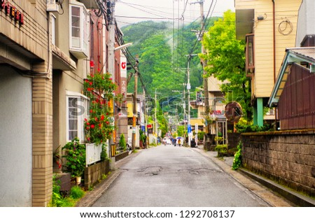 Yufuin ,Yufu ,Oita ,Japan - May 9th,2015 : Cityscape view of narrow street alley with Mount Yufu (Yufudake) background in small peaceful town calls Yufuin village where has Kinrinko Lake is located #1292708137