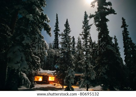 Yukon/Alaska trapline log-cabin fully illuminated at full-moon night in snowy winter.