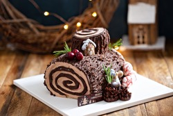 Yule log roll cake for Christmas decorated with chocolate ganache