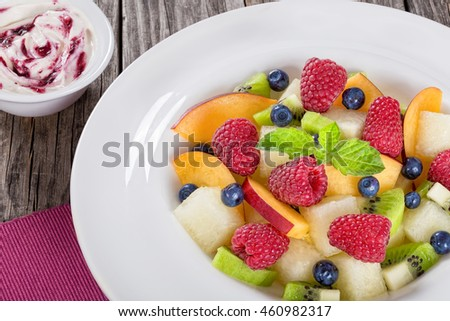 yummi fruit  and berry summer dessert salad decorated with mint leaves in white wide rim dish  on wooden boards and cream sauce bilberry dip, view from above, close-up