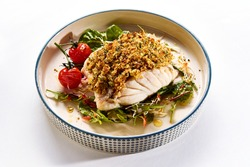 Yummy baked cod fish with breadcrumbs served on ceramic plate with fresh salad leaves and yummy cherry tomatoes