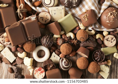 Yummy chocolate candies with nuts on wooden table