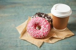 Yummy donuts with sprinkles and paper cup on wooden table