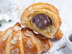 Yummy freshly croissant, sliced almonds, with chocolate filling cut, close up
