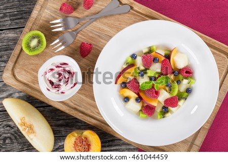 yummy fruit  and berry summer dessert salad decorated with mint leaves in white wide rim dish  on wooden cutting boards and cream sauce bilberry dip, view from above, close-up