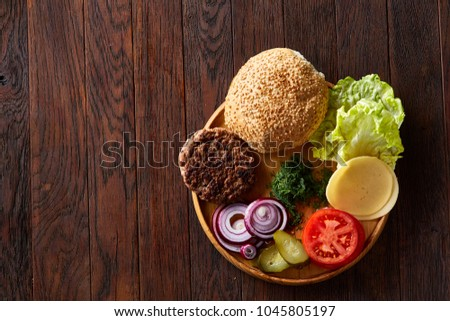 Yummy hamburger ingredients artistically organized on wooden plate, close-up, top view, selective focus