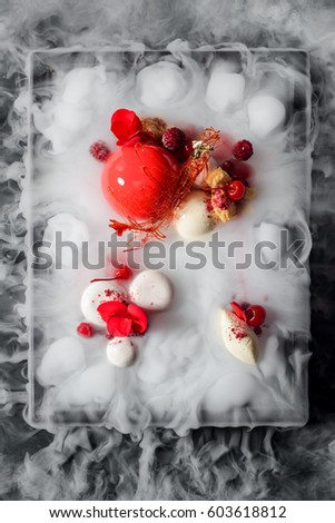 Shutterstock Yummy mousse cake, yogurt spheres, cherries, raspberries, a caramel decoration and fresh flowers in dry ice mist, a top-view image. Molecular food.