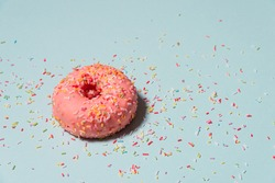 Yummy pink donut with colorful sprinkles on blue background.