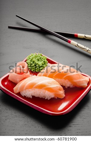 Yummy salmon. A close-up of chopsticks and a square plate with two pieces of salmon nigiri, wasabi and ginger.