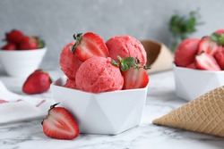 Yummy strawberry ice cream on white marble table