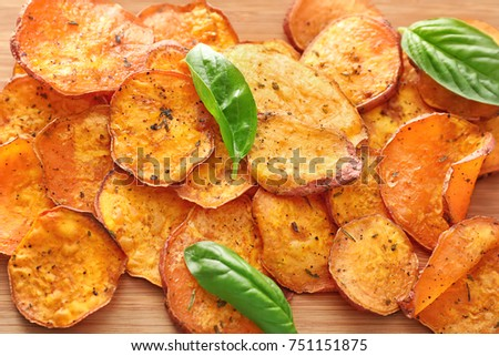 Yummy sweet potato chips on wooden background