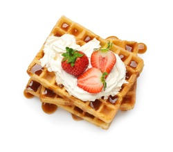 Yummy waffles with whipped cream, strawberries and caramel syrup on white background, top view