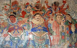Yungang Grottoes near Datong in Shanxi Province, China. Colorful fresco in a cave at Yungang with characters from history and legend. Yungang Buddhist cave art and sculptures UNESCO world heritage.